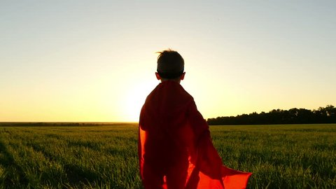A child in a superhero costume in a red raincoat is running on a green lawn against the backdrop of a sunset simulating a flight, at a slow pace