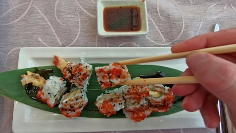 SLOW MOTION: chopsticks picking Uramaki of shrimp tempura, cheese, avocado and tobiko caviar dipped in soy sauce bowl. Japanese fusion food, Asian cultures. Healthy food, light diet concept.