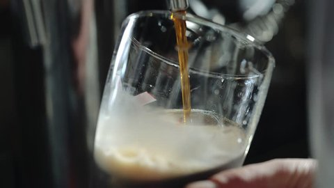 Bartender pours a dark beer in glass. Close-up.