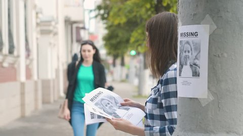 Girl volunteer handing out leaflets about the missing child,slow mo