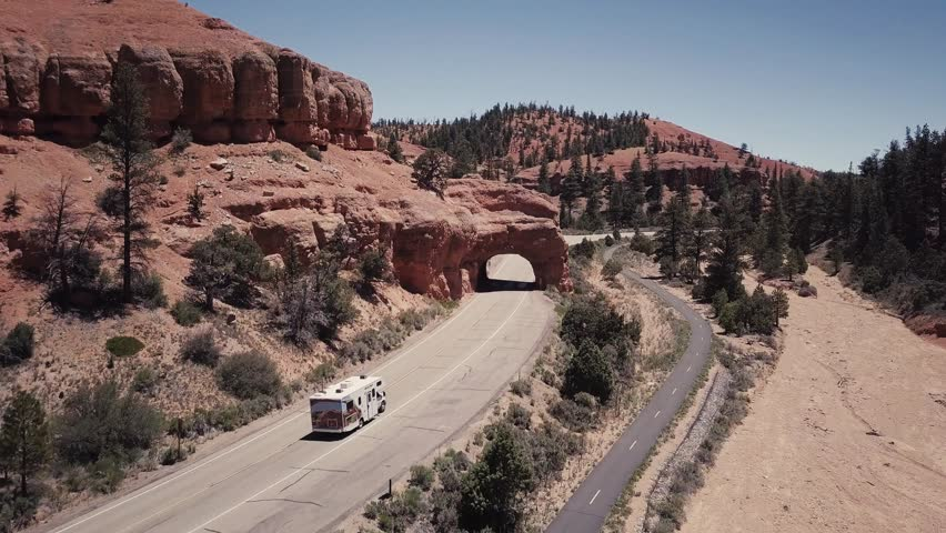The drone follows a camper in Bryce on a sunny day with a clear blue sky in the USA Aerial Drone Footage 4K