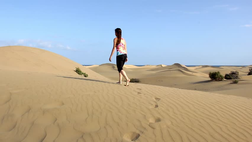 Young woman walks barefoot on sand dunes with sea views on the background in Maspalomas, Gran Canaria. Lonely lady exploring desert in Canary Islands, Spain. Travel adventure, summer holidays concept | Shutterstock HD Video #1012043702