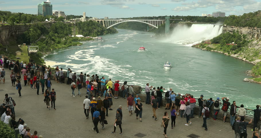 Niagara Falls, Canada - July 25, 2017: Crowds of summer vacation tourists walk by the landmark Horseshoe Falls in Niagara Falls Ontario Canada