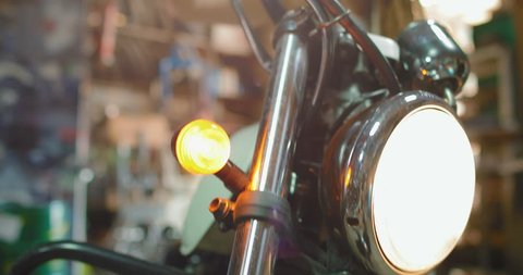 A female biker with dreadlocks and sunglasses on her head repairs her motorcycle in the garage. The girl controls the accelerator.  in slow motion