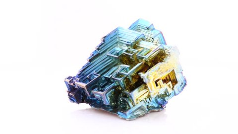 Footage of amazing colorful blue-gold Bismuth Gemstone macro closeup isolated on white rotating platform (30 fps)
