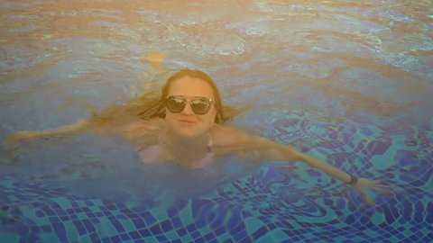 Beautiful girl in the pool. Summer sun. Slow motion