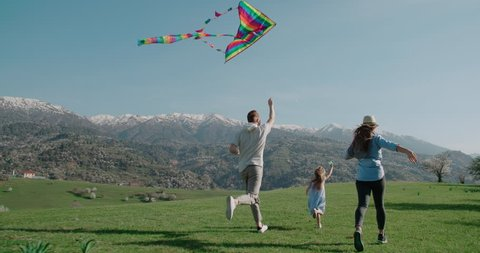 young family running in the mountains, flying kite in slow motion, happy family concept, family idyll