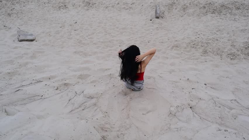 Young brunette girl in the desert hot on the sand  | Shutterstock HD Video #1012110152