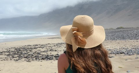 Back view of young woman with straw hat walking on Caleta Famara beach and looking to the ocean, Lanzarote, Spain
