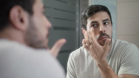 Young hispanic people and male beauty. Latino person grooming in bathroom at home for morning routine and body care. White metrosexual man applying lotion for anti-aging treatment around eye