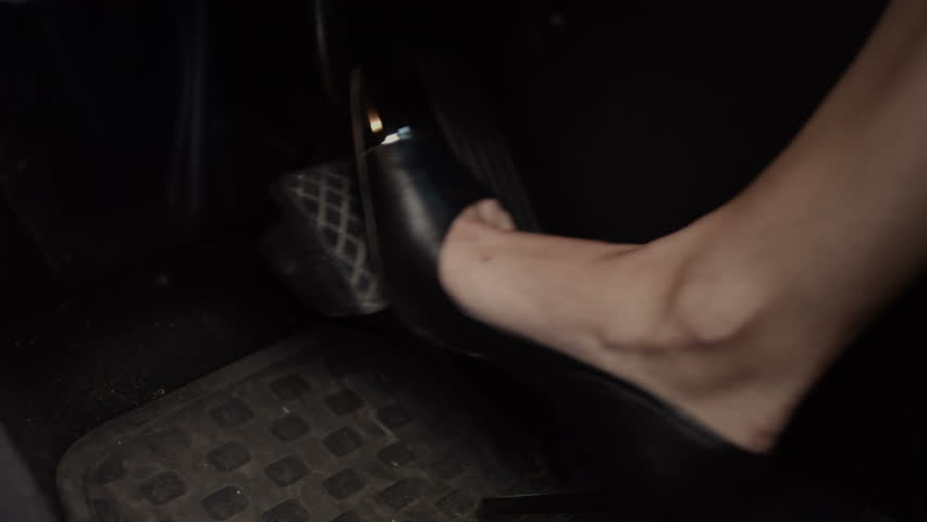 Closeup of female leg in stylish black high heel shoes pressing the brake pedal during driving. Female driver in high heels driving car and pressing the brake pedal.