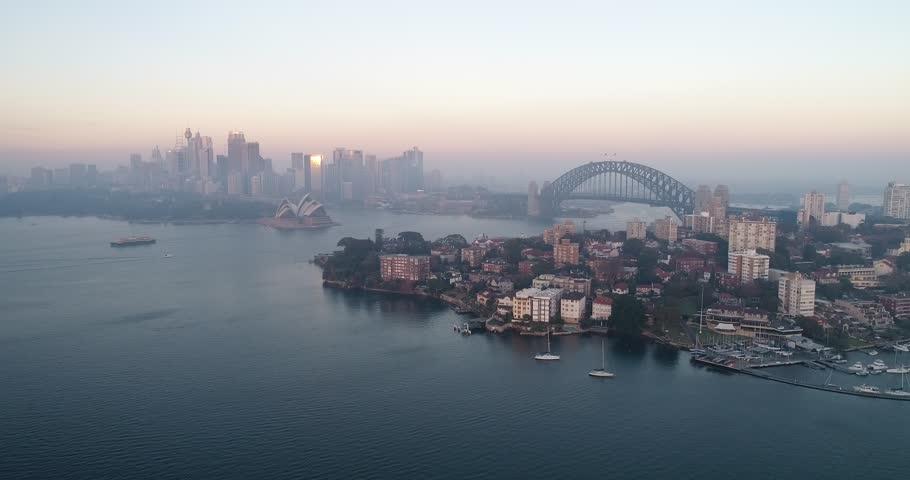 Around Kirribilli waterfront facing Sydney city architectural landmarks in aerial panning at sunrise.