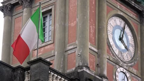 4K. Italian flag waving in the wind, located in Piazza Dante, Naples. Italy flag is a tricolour. Green, white and red are the national colors. Nearby there is a large clock-Adrian