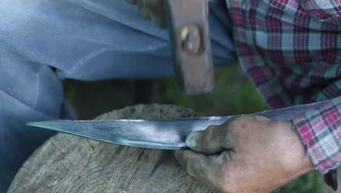 sharpen a steel blade with a hammer in a traditional workshop. Tool knife for mowing grass.