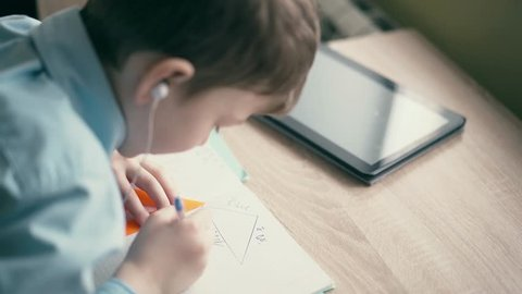 CU: Boy do school homework, writes a ballpoint pen in a notebook. In the ears are inserted headphones, on the table is a tablet computer and school supplies.
