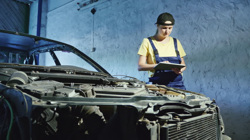 A woman mechanic uses a digital tablet in an auto repair garage. Mechanics overhauling an engine in the garage. Ordering new car parts via the Internet