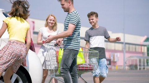 Happy family with shopping cart with purchases in parking lot near supermarket. People putting bags with food into car trunk and sits in car. Mom, Dad, Children having fun outdoors near grocery store.