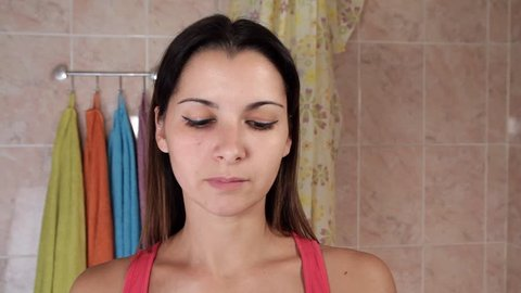 Young woman applying anti-wrinkles cream. Beautiful girl puts cream on the face in the bathroom. Attractive young woman caring for the skin in front of the mirror.