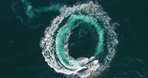 Upper view white motorboat sails making foamy circles on deep blue sea surface
