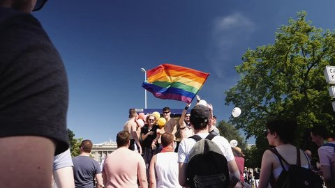 STRASBOURG, FRANCE - JUN 10, 2017: Strasbourg University building with girl dancing sensually on a gay truck with male waving rainbow flag in slow motion at LGBT GLBT visibility march pride FestiGays