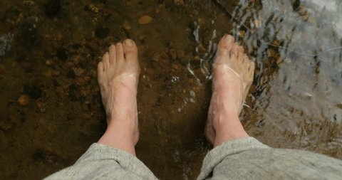 Woman resting her bare feet in a cool mountain stream, river, or lake