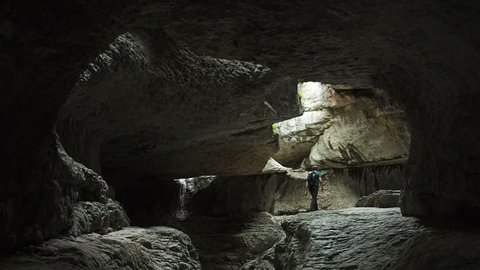 Hiker Man Exploring Dark Mysterious Cave. Explore Earth People Nature Travel Concept. Hiker Man Hiking Enjoying Travel Vacation Outdoor