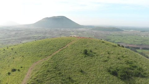 Aerial drone shot of hill rising up with volcano in the background in Jeju, South Korea in 4K