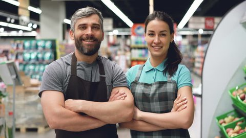 Portrait of two supermarket employees attractive people in aprons standing inside shop, smiling and looking at camera. Shelves with food and drinks are visible.