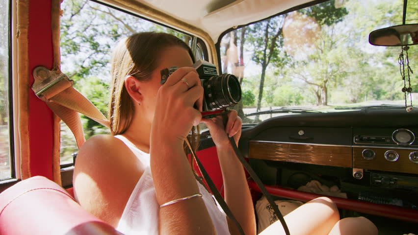 Beautiful girl taking pictures in a car with friend during road trip. Shot with a RED camera. 4k footage.