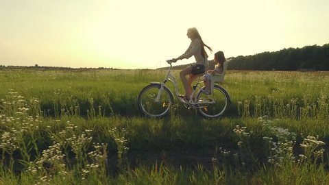 Mother and daughter have bike ride on nature. Summertime activity. Aerial