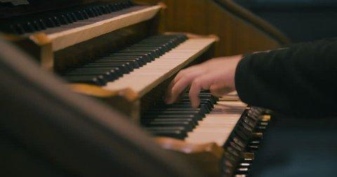 Detail of a man playing a church organ.