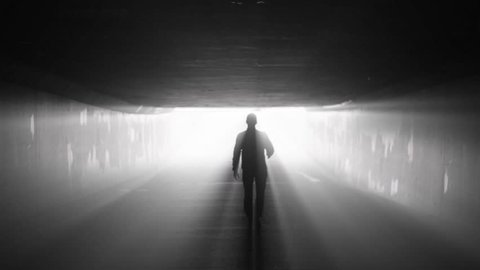 Silhouette of man walking in tunnel to the light. Concept of afterlife