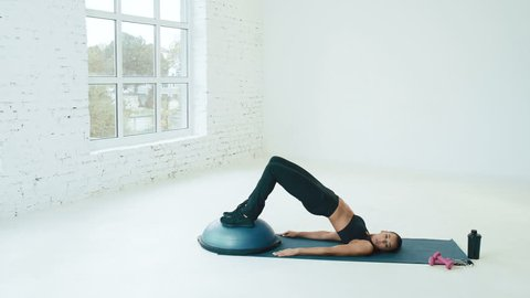 Beautiful girl wearing sport at background near big windows, doing exercises with bosu on mat, push ups