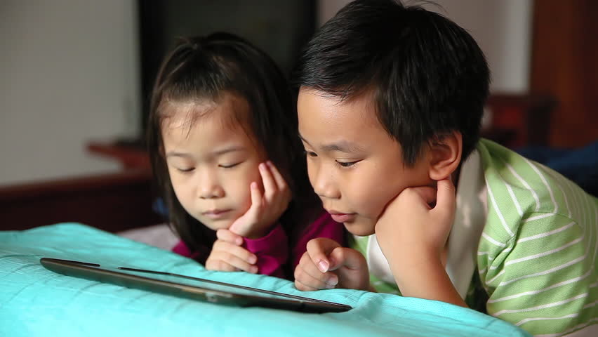 Asian children using digital tablet and lying prone on bed. Conceptual about using E-learning technologies and sibling relationship.
