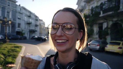 Close up footage of a young woman face in glasses eating an ice cream from malee hand. Friendship, having fun, smiling. Outside on the street. Sunny day