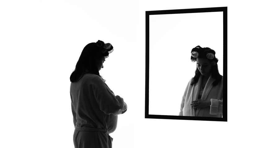 Pregnant depressed woman looking in mirror alone, imagining husband hugging her | Shutterstock HD Video #1012310072