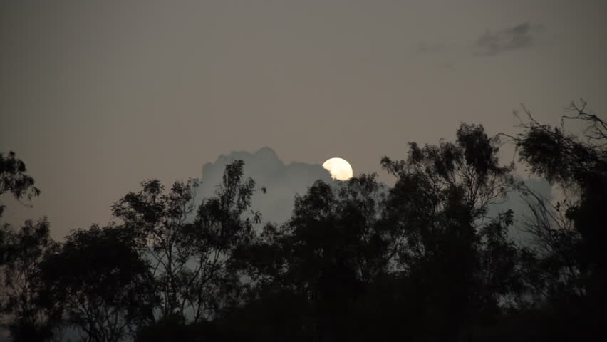 A long shot of the moon as the clouds try to cover it. | Shutterstock HD Video #1012333982