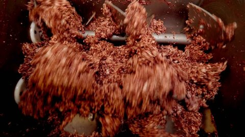 Processing lard or meat in minced meat on a huge meat grinder at a meat factory closeup.