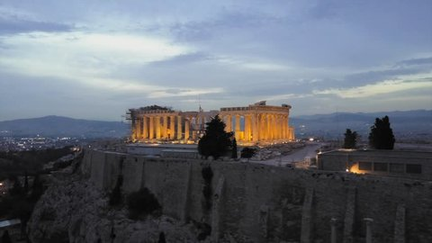 Athens Acropolis and Parthenon in evening at sunset. beautifully lit light up at. Aerial drone view from above the Greek capital. City and city center in background. 4k view in low light.