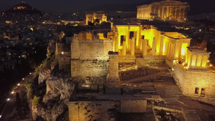 Athens Acropolis and Parthenon at night. Beautifully lit light up at. Aerial drone view from above the Greek capital. City and city center in background. 4k view in low light.