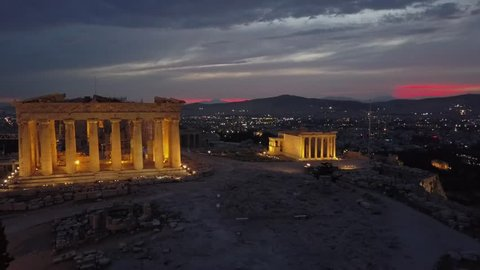 Temple beautifully lit light up at sunset. Athens Acropolis and Parthenon in evening . Aerial drone view from above the Greek capital. City city center, red orange sunet  in background