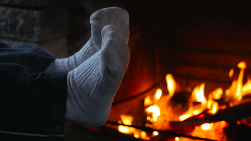 Child wet feet in pantyhose are heated by fireplace in cold weather. Tired family after long walk resting in cabin