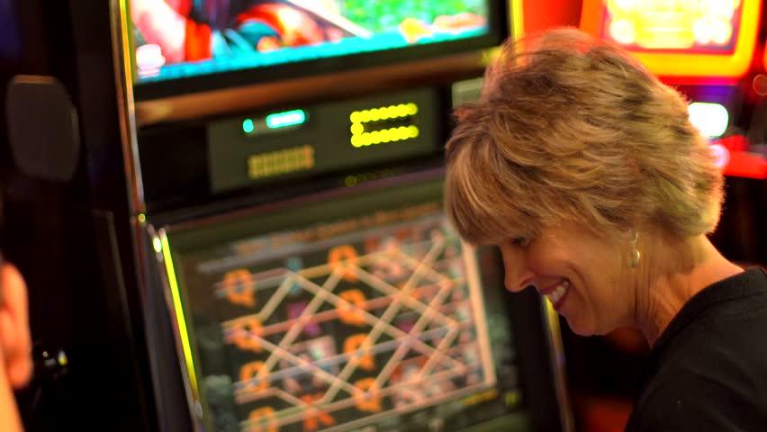 Older caucasian woman plays slot machine and wins | Shutterstock HD Video #1012405712