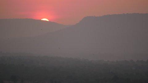 Birds Flying on Pha Taem National Park , Sunrise behind The Mountain