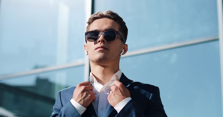 Attractive young businessman using wireless earphones standing outside. He wearing sunglasses and looks away. Communication, finance, business people, interns, CEO. Close up. Shot on Red Epic