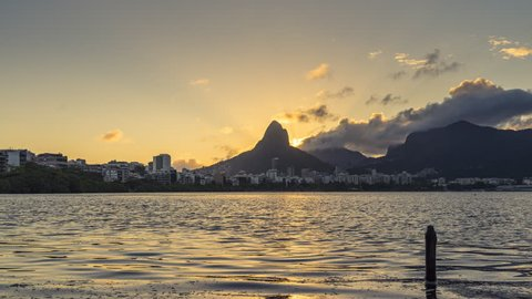 Sunset over city of Rio De Janeiro with iconic Dois Irmaos Mountains, Brazil. Timelapse