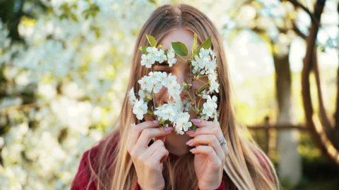 Pretty Ukrainian girl with nice smile hiding face behind flowering twigs. Attractive young Caucasian woman with long hair looking at camera. Springtime. Countryside.