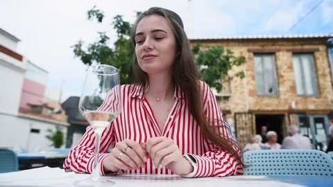 Young attractive woman checks the restaurant bill, becomes shocked, takes her bag and wants to quit without paying. Outdoors restaurant. Woman has no money to pay the bill.