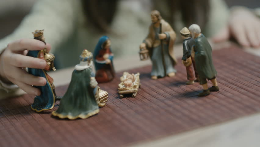 Magi and shepherds on the Holy Infant figurines.Children playing with the figurines