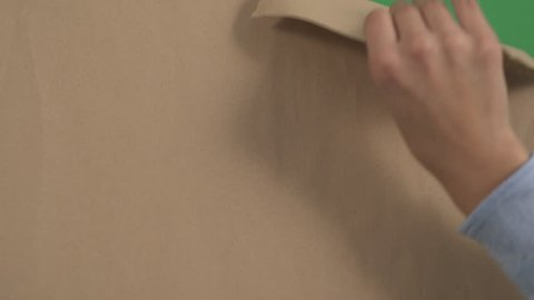 Hand ripping a brown paper.